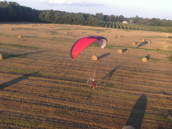 Andre Zeman flying his powered paraglider low over hay bales